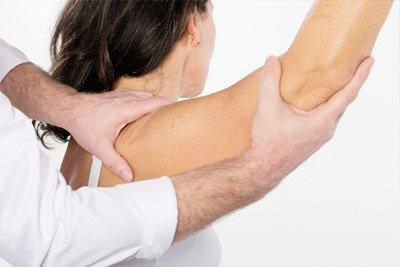 врач держит плечо
