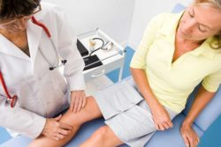 врач смотрит ногу
