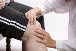 врач смотрит колено