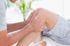 доктор делает массаж коленки