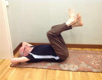 пожилой мужчина лежа сгибает ноги