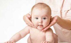 врач держит шею ребенка