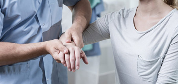 Male physiotherapist is massaging female patient hand